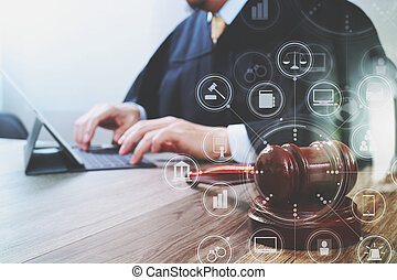justice and law concept. Male judge in a courtroom with the gavel, working with digital tablet computer docking keyboard on wood table, virtual interface graphic icons diagram