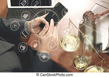 justice and law concept. Male lawyer in office with the gavel, working with smart phone, digital tablet computer docking keyboard, brass scale, on wood table, virtual interface graphic icons diagram