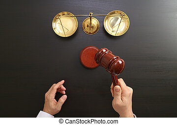 justice and law concept. Top view of Male judge hand in a courtroom with the gavel and brass scale on dark wood table
