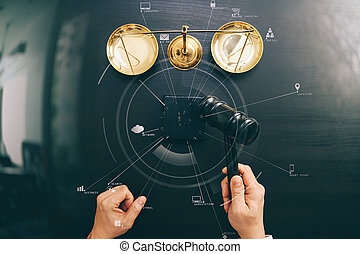 justice and law concept. Top view of Male judge hand in a courtroom with the gavel and brass scalr on dark wood table with Vr diagram