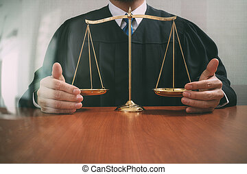 justice and law concept.Male judge in a courtroom with the balance scale on wood table