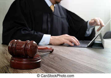 justice and law concept.Male judge in a courtroom with the gavel,working with digital tablet computer docking keyboard on wood table