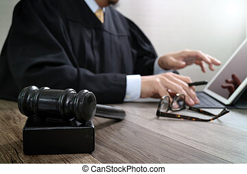 justice and law concept.Male judge in a courtroom with the gavel,working with digital tablet computer docking keyboard on wood table,eyeglass