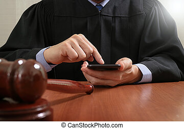 justice and law concept.Male judge in a courtroom with the gavel,working with smart phone computer on wood table