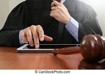 justice and law concept.Male judge in a courtroom with the gavel,working with digital tablet computer on wood table