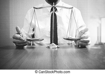 justice and law concept.Male lawyer in the office with brass scale on wooden table,black and white