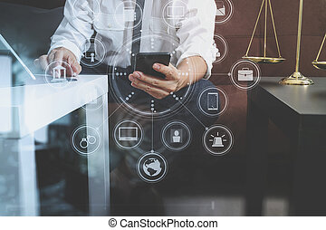 Justice and Law context. Male lawyer hand sitting on sofa and working with smart phone, digital tablet computer docking keyboard with gavel and document on living table at home, virtual interface graphic icons diagram