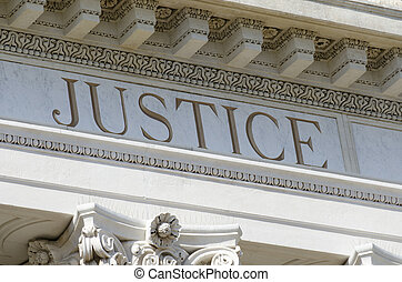 justice word engraved on courthouse pediment