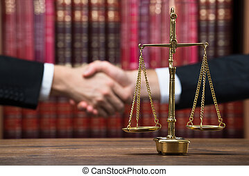 Justice Scale On Table With Judge And Client Shaking Hands -...