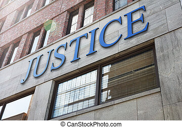 Justice sign on modern building in city