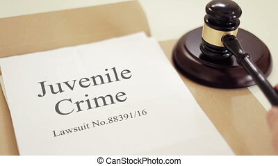 Juvenile offending lawsuit verdict folder with gavel placed on desk of judge in court
