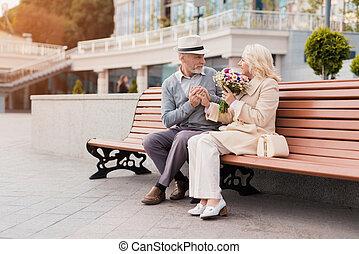 két, nyugdíjas, vannak, ülés, képben látható, egy, bírói szék, alatt, a, alley., a, idős, ember, gave, a, nő, flowers., ő, fog, neki, kéz