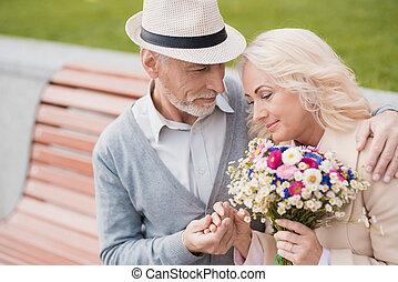két, nyugdíjas, vannak, ülés, képben látható, egy, bírói szék, alatt, a, alley., egy, öregedő bábu, szelíden, fog, neki, kéz