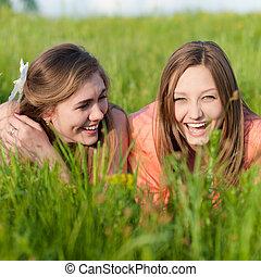 két, tizenéves lány, friends nevetés, alatt, zöld fű