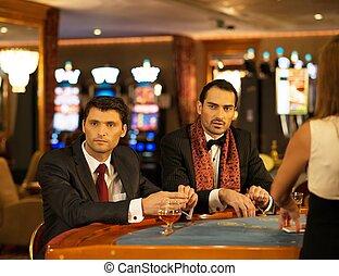 két, young bábu alkalmaz, mögött, hazárdjáték, asztal, alatt, egy, kaszinó