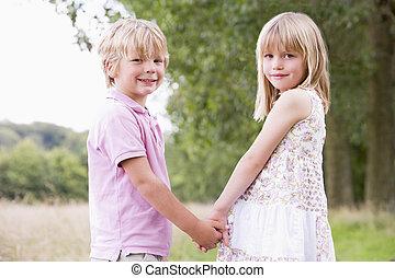 két, young gyermekek, álló, szabadban, hatalom kezezés, mosolygós
