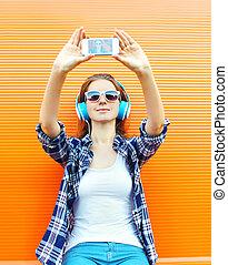 kühl, m�dchen, marken, selbstporträt, auf, smartphone, und, hört, zu, musik, in, kopfhörer