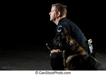 a K9 police officer with his German Shepherd at night.
