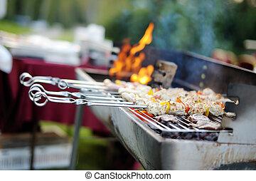 Kabobs grilled with vegetables on metal skewers - Kabobs are...