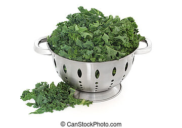 Kale green cabbage in a stainless steel colander and loose, over white background.
