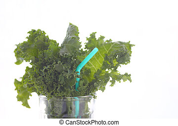 Kale leaves in glass with straw