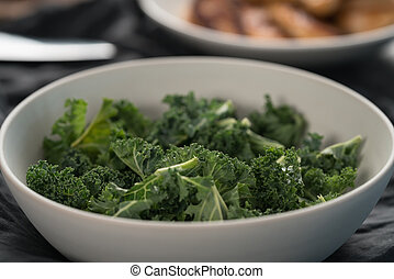 kale salad leaves in white bowl on linen napkin with other ingredients on background