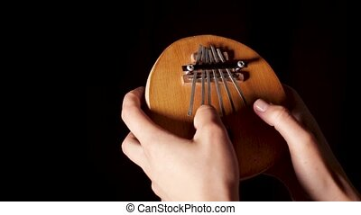 Close-up of an ancient and popular African reed plucked musical instrument - a lamellophone on a black isolated background. A person plays the kalimba. Footage shot with professional artificial lighting in 4K in real time