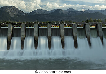 Wide time exposure of the spillway on the Kananaskis hydroelectric dam on the Bow River, with Canadian Rockies in the background in Alberta, Canada
