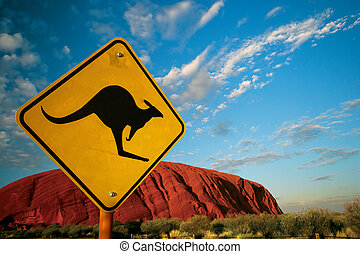 A Kangaroo warning sign in front of Ayers Rock in the Australian outback.