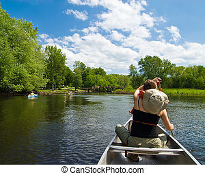 Young woman paddling on a gentle little river