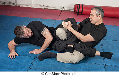 Kapap instructor demonstrates ground fighting techniques ...
