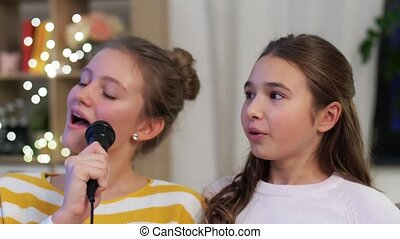 teenage girls with microphone singing at home - karaoke and ...