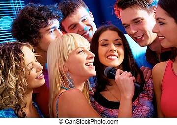 Karaoke party - Image of happy young woman sings a song in...