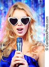 karaoke - Portrait of a beautiful blonde girl singing with a...