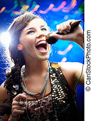Karaoke - Portrait of a glamorous girl holding a mike and...