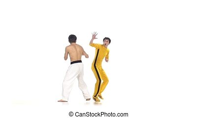 karate and taekwondo sparring: strikes . Slow motion, One of karate in the yellow suit