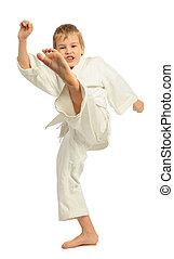 Karate boy kicking by a left leg