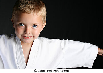 Karate Boy - Young boy wearing his karate uniform on a black...