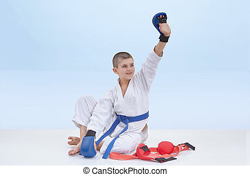 Karate boy with a blue belt is sitting near karate outfit