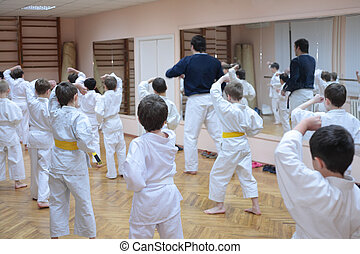 karate boys training in sport hall, focus on left boy in...