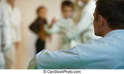 Karate coach with children in gym