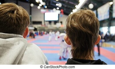 Karate competition - two teenagers boys looking at fighting...
