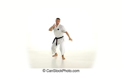 Karate. Man in a kimono hits foot on the white background. Slow motion