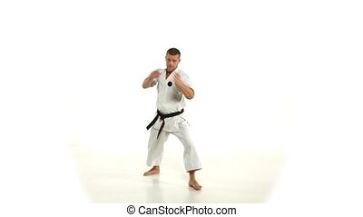 Karate. Man in a kimono hits foot on the white background.