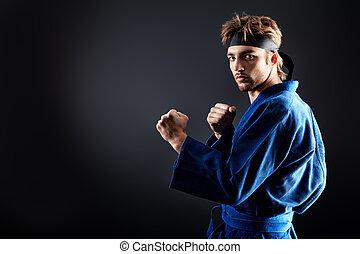 karate man - Martial arts fighter posing at studio.