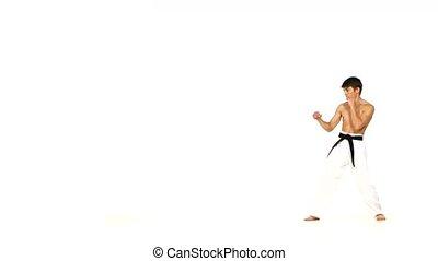karate or taekwondo man jumping, high kick and fist punch on...