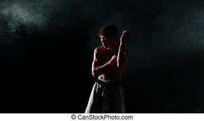 Karate or taekwondo training man punches smoke, close up....