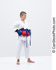 Karateka boy with a blue belt and overlays on a light background