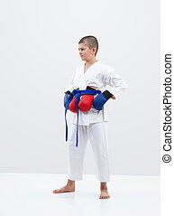 Karateka boy with blue overlays on the hands and red overlays behind the belt
