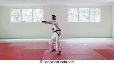 Front view of a teenage mixed-race male judoka wearing white judogi, warming up before a training in a gym, striking a pose, stretching his leg up and kicking the air in slow motion.